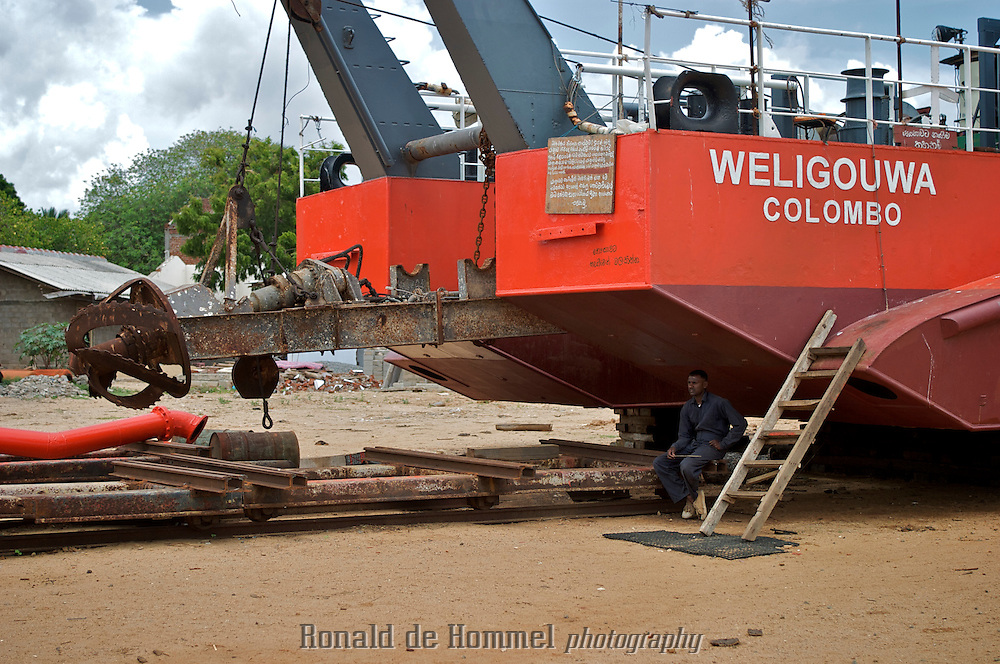 A dredging ship that was increasing the size of Kirinda Harbour in South Sri Lanka was thrown onto the shore by the 2004 tsunami. Tourists have their photos taken in front of the boat