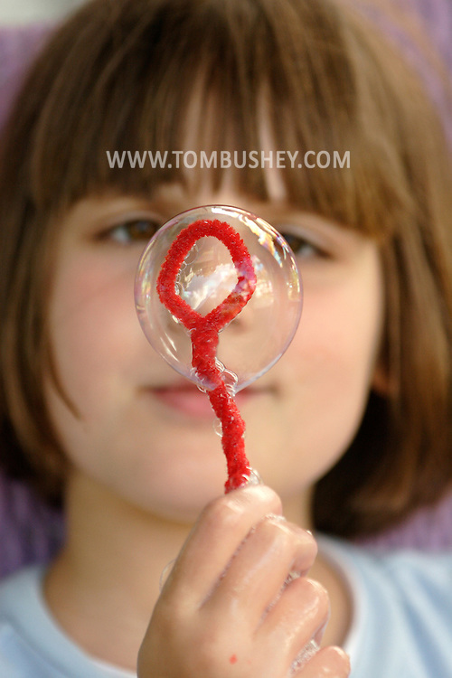 Middletown, NY  - An 8-year-old girl looks at a bubble she made with a home-made bubble wand on June 27, 2007.