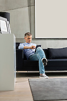 Full-length of Middle-aged man using tablet PC on sofa