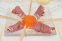 prosciutto wrapped on glass dish with stick bread side view from above close-up
