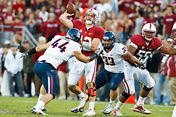 November 6, 2010; Stanford, CA, USA;  Stanford Cardinal quarterback Andrew Luck (12) is pressured while throwing a pass by Arizona Wildcats defensive end Ricky Elmore (44) during the first quarter at Stanford Stadium.