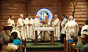 PRICE CHAMBERS / NEWS&amp;GUIDE<br /> Bishop Paul D. Etienne of the Diocese of Cheyenne kisses a book of the gospels during Mass on the 75th anniversary of the Chapel of the Sacred Heart.