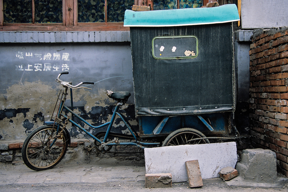 This old covered tricycle and it's owner can be hired as a taxi to help you find your way through the maze of an old hutong.