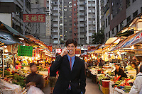 Young business man talking on mobile at street market