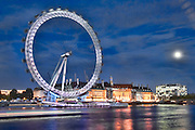 London Eye at night with the moon.