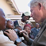 July 13, 2006 - President Clinton plays with a baby outside the antiretroviral treatment center, Karabong Clinic, at Mafeteng Hospital in Lesotho. Karabong clinic is the second largest government-run treatment facility in Lesotho with 1200 patients receiving ART. Photo by Evelyn Hockstein