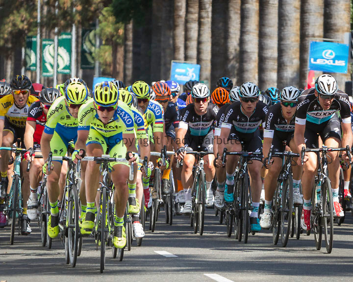 Sunday, May 10, 2015<br /> Tinkoff-Saxo and Etixx-Quick-Step teams lead the peloton along L Street near the capitol building in downtown Sacramento, California, during Stage 1 of the <br /> Amgen Tour of California. Etixx-Quick-Step's MARK CAVENDISH (GBR), in the center of the peloton with the sun striking his face, won the stage in the time of 4h43'17&quot;.
