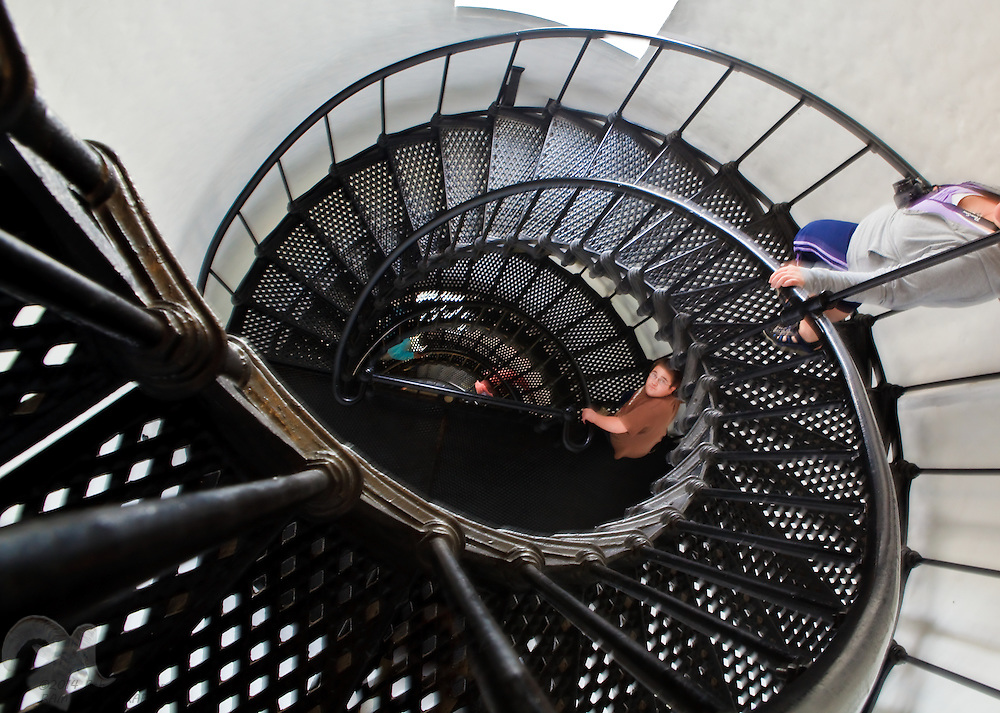 People descend a spiral staircase in the Yaquina Head Lighthouse on the Oregon coast. The lighthouse is Oregon's tallest at 93 feet.