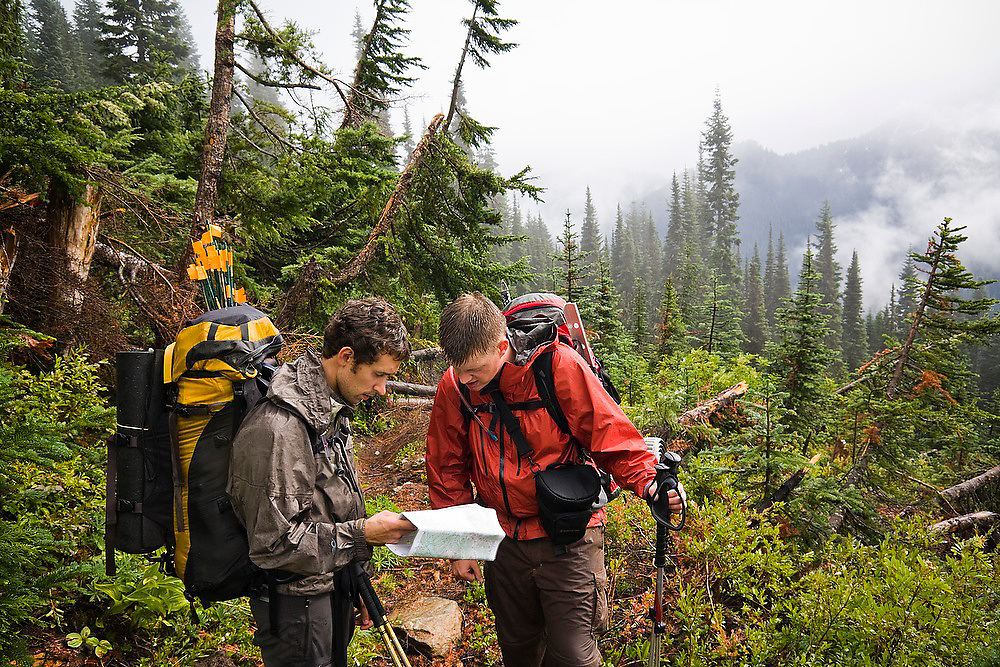 Tired and wet climbers intending to summit Glacier Peak inspect their topo map in Glacier Peak Wilderness, Washington.