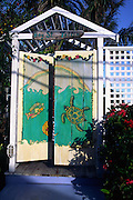 double door painted with turtle & fish; white frame & fence; Hopetown; Elbow Cay; Bahamas
