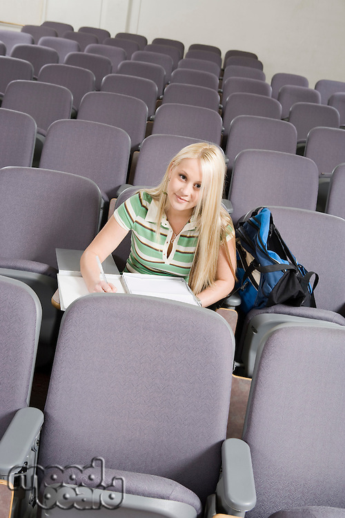 Female student writing in lecture hall