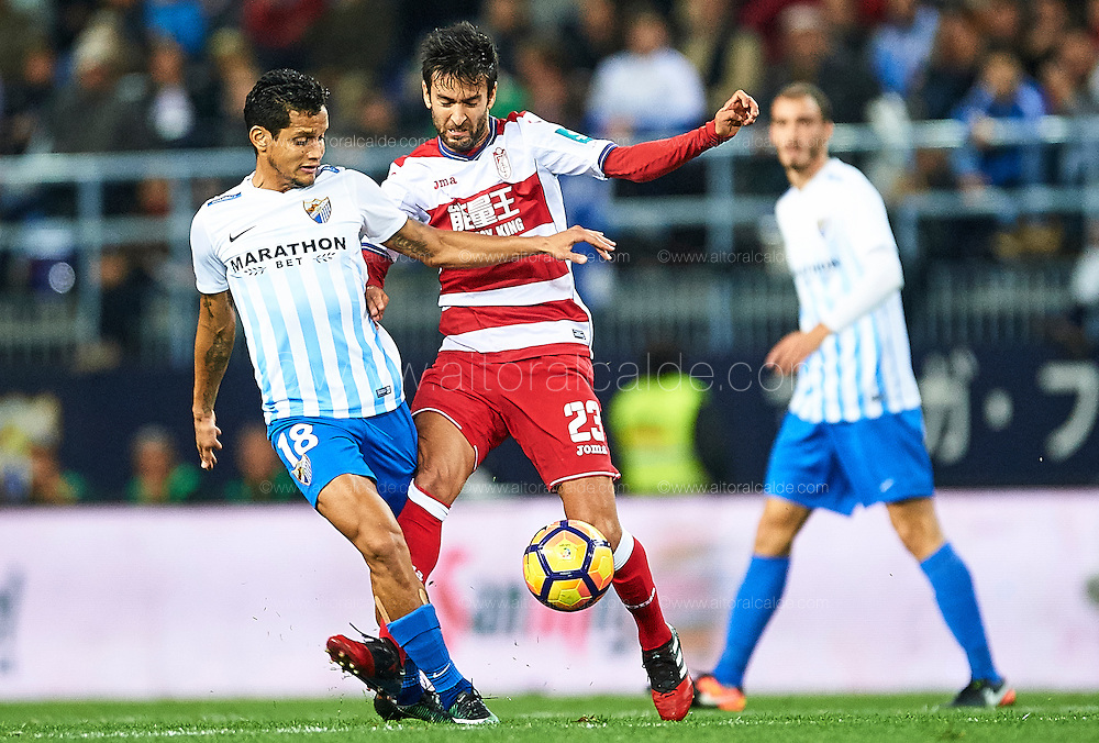 MALAGA, SPAIN - DECEMBER 09:  Roberto Rosales of Malaga CF (L) competes for the ball with Alberto Bueno of Granada CF (R) during La Liga match between Malaga CF and Granada CF at La Rosaleda Stadium December 9, 2016 in Malaga, Spain.  (Photo by Aitor Alcalde Colomer/Getty Images)