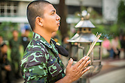 26 NOVEMBER 2012 - BANGKOK, THAILAND:  A soldier prays in the courtyard at Siriraj Hospital, outside the wing housing the King of Thailand, in Bangkok. Siriraj was the first hospital in Thailand and was founded by King Chulalongkorn in 1888. It is named after the king's 18-month old son, Prince Siriraj Kakuttaphan, who had died from dysentery a year before the opening of the hospital. It's reported to one of the best hospitals in Thailand and has been home to Bhumibol Adulyadej, the King of Thailand, since 2009, when he was hospitalized to treat several ailments. Since his hospitalization tens of thousands of people have come to pay respects and offer get well wishes. The King's 85th birthday is on Dec 5 and crowds at the hospital are growing as his birthday approaches. The King is much revered throughout Thailand and is seen as unifying force in the politically fractured country.       PHOTO BY JACK KURTZ