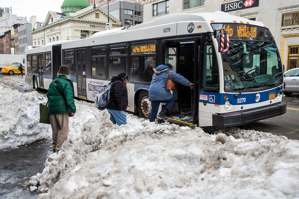 Some people wrapped up in warm clothes, carefully walk over snow mounds to board the M14D bus on 728 Amsterdam Avenue, New York City,  New York, United States of America, after the snowstorm in January 2016. The snowstorm brought more than 2 feet of snow in many areas, which broke many records.  (photo by Andrew Aitchison / In pictures via Getty Images)
