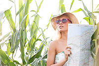 Woman holding map while standing amidst plants outdoors