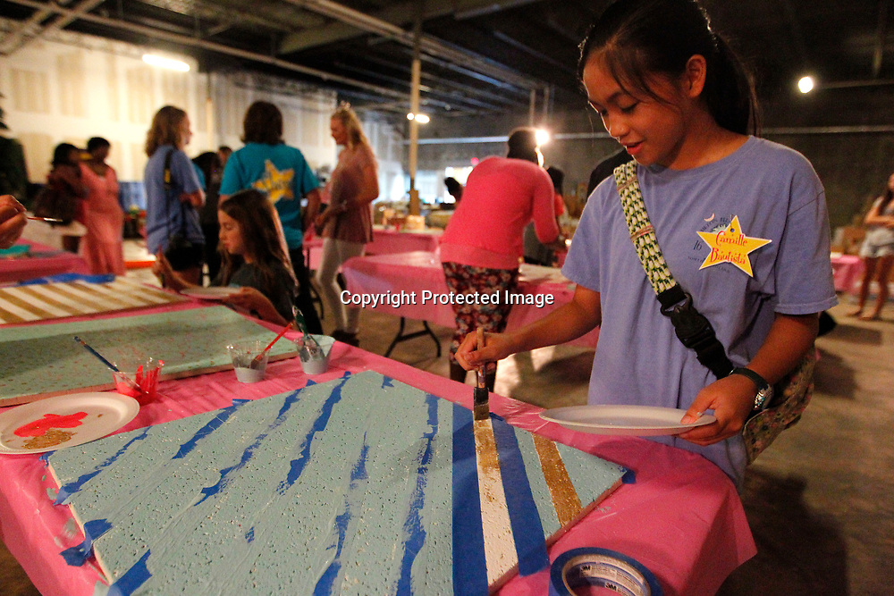 Camille Bautista, 12, of Tupelo, works on painting her bulletin board projects at the Junior Auxilary's SHINE camp Tuesday night at HealthWorks in Tupelo. The camp promotes self esteem through acting, art and physical activity.
