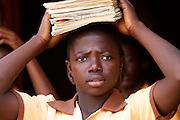A school girl carrying her school books on her head. Tonga Junior High School, Ghana.