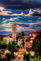 """""""The sunset illuminates the bell tower of Santa Maria Maggiore - Assisi""""…<br /> <br /> After a progressive but slow ascent up to the mountaintop of Assisi, I took time to pause, look over my shoulder, and truly appreciate all I had seen. God always seemed to illuminate my forward path; however, He also left a glow of remembrance from where the journey began. This evening view is from the Basilica di Santa Chiara (Basilica of St. Clare), a 13th-century church that houses the relics of St. Clare, friend and protégé of St. Francis of Assisi, and the 12th-century crucifix that spoke to St. Francis at San Damiano. The view is a rear view of the church and campanile of Santa Maria Maggiore, the first cathedral of Assisi which was built near the Roman city walls of the 4th century. The crypt under the apse of the present church is the oldest surviving part of the structure and dates to the 9th or 10th century. Santa Maria Maggiore remained the cathedral of Assisi until 1035 when San Rufino assumed this function."""