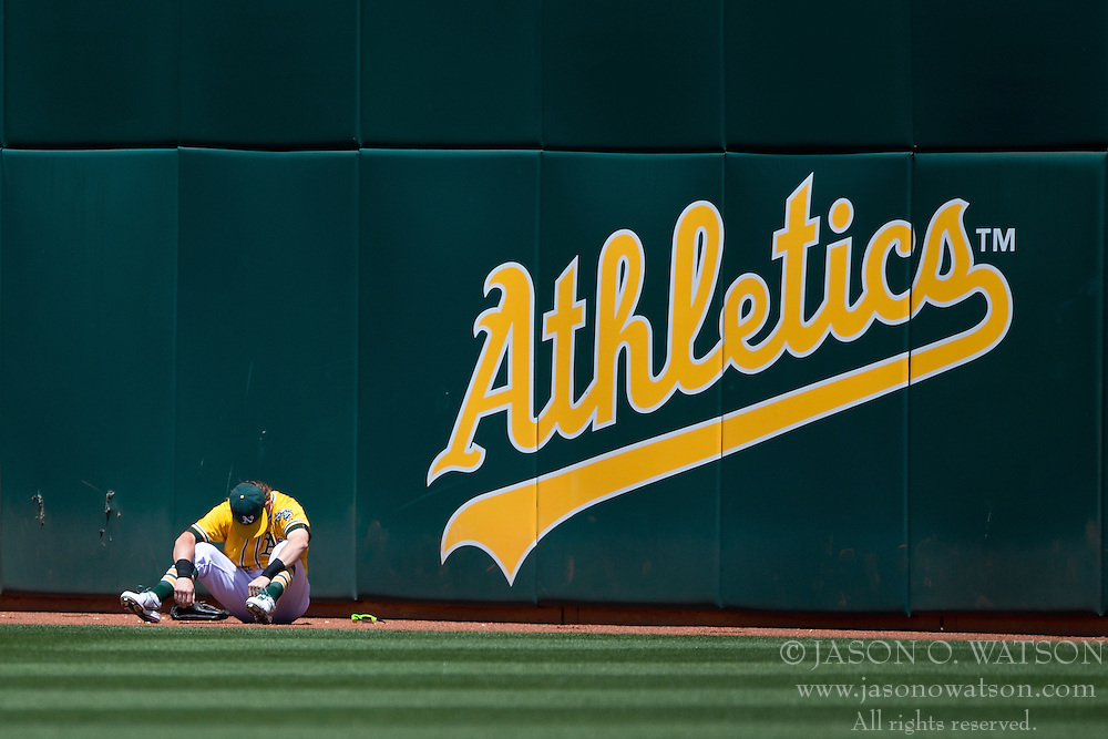 OAKLAND, CA - JUNE 18:  Josh Reddick #22 of the Oakland Athletics sits on the warning track after colliding with Billy Burns (not pictured) in the outfield attempting to field a fly ball hit off the bat of Melvin Upton Jr. (not pictured) of the San Diego Padres during the eighth inning at O.co Coliseum on June 18, 2015 in Oakland, California. The San Diego Padres defeated the Oakland Athletics 3-1. (Photo by Jason O. Watson/Getty Images) *** Local Caption *** Josh Reddick