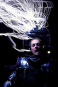 "Austin Richards of Santa Barbara, CA, is zapped by his homemade Tesla Coil. Richards wears a homemade robot outfit with a birdcage covering his head. The electrical ""lightning"" bolts his Tesla coil zaps him with do not do any harm because he is surrounded by metal that acts a Faraday cage, harmlessly channeling the charges to the ground and protecting his body from shocks. Richards performs these stunts for trade shows and parties. Here he is doing this for a block party near Santa Barbara. California, USA"