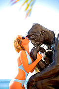 "A swimsuit-clad model kisses Rodin's ""Thinker""  statue on Florida's luxurious Fisher island"