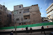 People on the street in front of a huge graffity showing the flag of the revolution in Idlib, Province of Idlib, Syria.