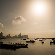 Wooden fishing boats silhouetted on the waterfront of Panama City, Panama, on Panama Bay, with the buildings of Punta Paitilla in the background in the distance.