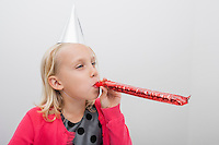Little girl wearing party hat blowing noisemaker at home