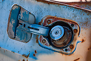 Rusted car gas cap cover, Idarado Mine ruins, Red Mountain Pass, Million Dollar Highway, San Juan Mountains, Colorado, USA. Winding through the San Juan Mountains, the Million Dollar Highway is the scenic 25 miles of US Route 550 between Silverton and Ouray. It was named for the twelve miles south of Ouray through the Uncompahgre Gorge to the summit of Red Mountain Pass. As part of the San Juan Skyway Scenic Byway, the Million Dollar Highway twists along sheer cliff edges with hairpin curves and few guardrails, past spectacular yellow foliage colors in autumn.