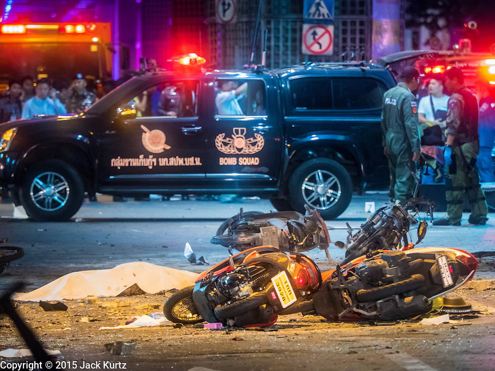 17 AUGUST 2015 - BANGKOK, THAILAND:         Thai police and bomb squad officers at the scene of an explosion in central Bangkok Monday, one of the dead is under a sheet in the right corner of the photo. An explosion at Erawan Shrine, a popular tourist attraction and important religious shrine, in the heart of the Bangkok shopping district killed at least 19 people and injured more than 120 others, mostly foreign tourists, during the Monday evening rush hour. Twelve of the dead were killed at the scene. Thai police said an Improvised Explosive Device (IED) was detonated at 18.55. Police said the bomb was made of more than six pounds of TNT stuffed in a pipe and wrapped with white cloth. Its destructive radius was estimated at 100 meters. The Bangkok government announced that public schools would be closed Tuesday as a precaution. PHOTO BY JACK KURTZ