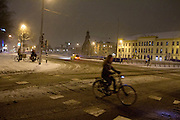 Een meisje fietst 's avonds in de sneeuw over het Smakkelaarsveld in Utrecht.<br /> <br /> A girl is cycling in the evening at Smakkelaarsveld in Utrecht.