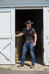 rugged cowboy opening up a barn door
