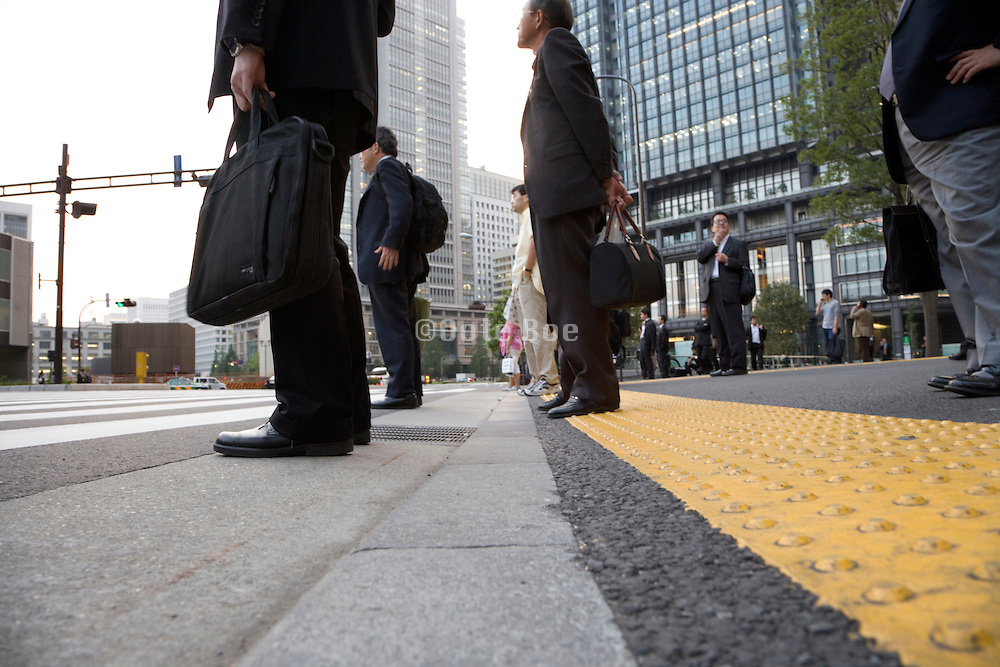 businesspeople waiting for red light to turn green at a pedestrain crossing Tokyo Japan