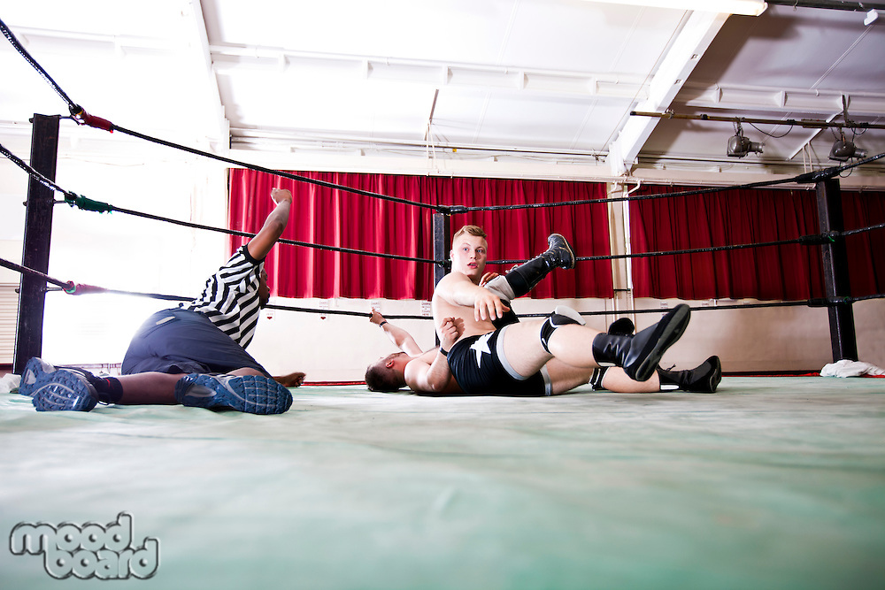Wrestlers pinning down rival while referee counting during match