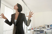 Businesswoman standing in office pressing hands and face against glass.