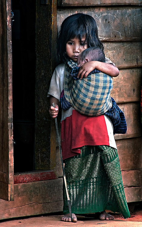 A Khamu village girl cares for her sister in northern Laos.