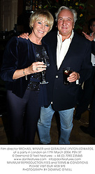 Film director MICHAEL WINNER and GERALDINE LYNTON-EDWARDS, at a party in London on 17th March 2004.PSN 37