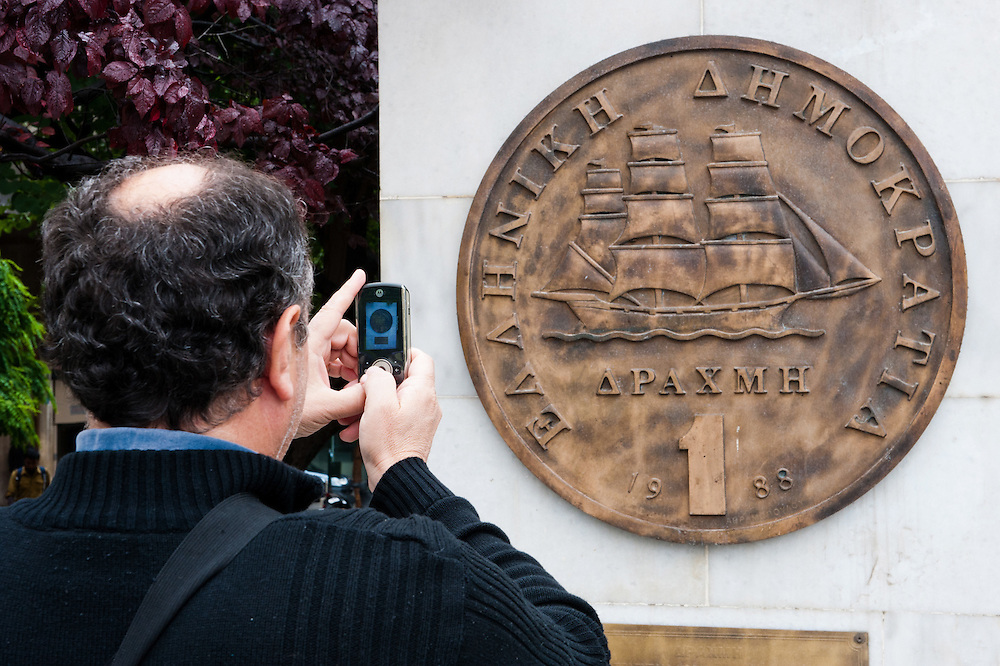 Man photographing with his mobile phone a plaque portraying an old drachma coin, which was replaced by the euro in 2002, outside Athens City Hall