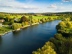 The afternoon sun illuminates the lush English landscape and the River Thames at Aston near Henley-On-Thames, Oxfordshire as the colours of autumn behind to appear on the trees. Henley On Thames, October 01 2018.