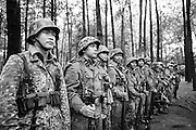 Indonesian men dressed up as German Waffen-SS soldiers stand in formation during a gathering of re-enactment enthusiasts in Cibubur, East Jakarta, Indonesia.<br /> Members of the 'Niederlande Kampfgruppe' group meet regularly to re-enact battles wearing Nazi Germany military uniforms and produce their own photos and videos. They claim that they do not do this because they identify ideologically with the Nazis, but because they are interested in World War II and military history. According to them, there is historical evidence that at least one Indonesian person was part of the 'Freiwilligen Legion Niederlande', the Dutch arm of the Waffen-SS, during World War II. Similar re-enactment groups exist in several cities across Indonesia, using the uniforms of Dutch, German and Japanese troops.