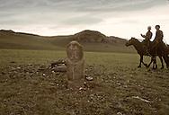 Mongolia. stone statue (Turkish 6th century)                       / Cavaliers passant devant un alignement de statues monolithes anthropomorphes. (Granit, VI-VIIIème siècle). / Ces statues représentent des  - 'idoles de pierre -  (KUN TCHULUU), typiques de l'art monumental des steppes d'Asie Centrale. D'après la coutume du culte des Ancêtres, ce genre de statue était érigée à la surface d'une tombe d'un noble guerrier, à l'époque des Turcs Célestes. Leur visage présente pratiquement toujours les mêmes caractéristiques : faciès plat, pommettes saillantes, yeux en amandes et moustache. L'idole, vêtue d'une robe avec ceinture, a le bras droit plié au niveau du coude et tient une coupe. (Sum de DJARGALAN, dans l'aymag de GOV ALTAY    Mongolie   / /10    L0006224  /  P0002615