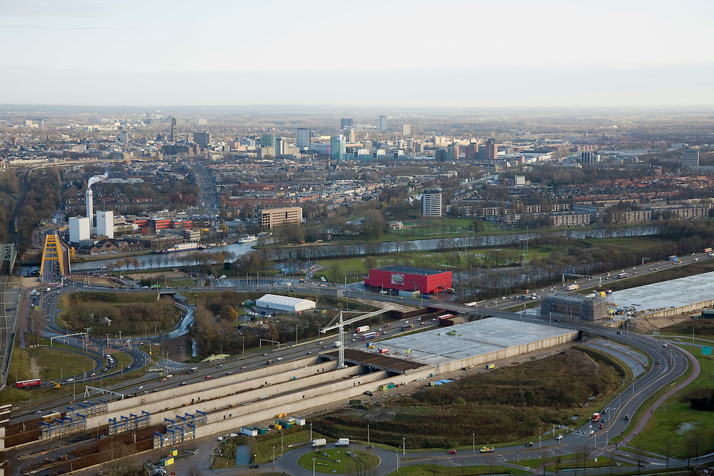 Nederland, Utrecht, Leidsche Rijn, 25-11-2008; aanleg bovengrondse tunnel voor de A2, de weg wordt verbreedhet rode gebouw is Vredenburg Leidsche Rijn, achter het Amsterdam Rijnkanaal de binnenstad van Utrechtoverkapping van de snelweg is noodzakelijk i.v.m. verbetering van de luchtkwaliteit en om de barrierewerking (tussen centrum van utrecht en de nieuwe wijk) tegen te gaanom het dak van de tunnel komt een park en zakelijke bebouwingaboveground tunnel construction for the A2, the highway is widenedthe red building is Vredenburg Leidsche Rhine (conert hall), behind the Amsterdam Rhine Canal city centre Utrechtcovering the highway is needed for improving air quality and minimize the barrier effect (between the center of Utrecht and the new district) controla park and commercial buildings will be realised on the roof of the tunneloverdekte snelweg, overkapping, landtunnel, covered highway, roof.  .luchtfoto (toeslag)aerial photo (additional fee required).foto Siebe Swart / photo Siebe Swart
