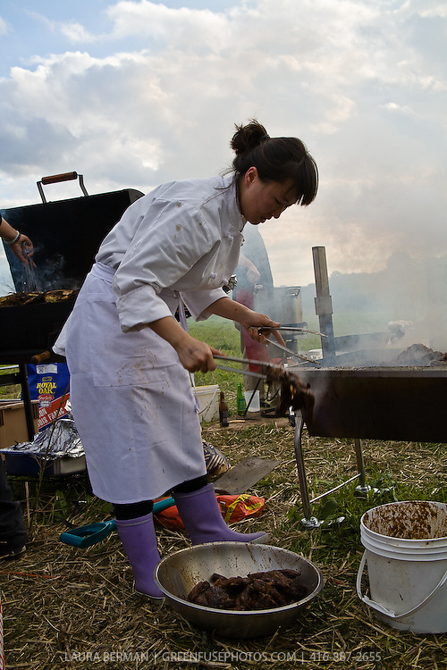 Food being prepared and cooked outdoors over flame and charcoal by chefs and cooks at the McVean harvest feast.