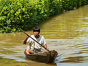 30 SEPTEMBER 2016 - SAI NOI, AYUTTHAYA, THAILAND: A man paddles his canoe through flood waters in Sai Noi on the Chao Phraya River. The Chao Phraya River, the largest river that runs through central Thailand, has hit flood stage in several areas in Ayutthaya and Ang Thong provinces. Villages along the river are flooded and farms are losing their crops due to the flood. This is the same area that was devastated by floods in 2011, but the floods this year are not expected to be as severe. The floods are being fed by water released from upstream dams. The water is being released to make room for heavy rains expected in October.      PHOTO BY JACK KURTZ