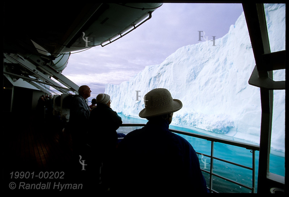Passengers aboard the Clipper Adventurer cruise ship crowd along upper deck to admire towering Disko Bay iceberg; Ilulissat, Greenland