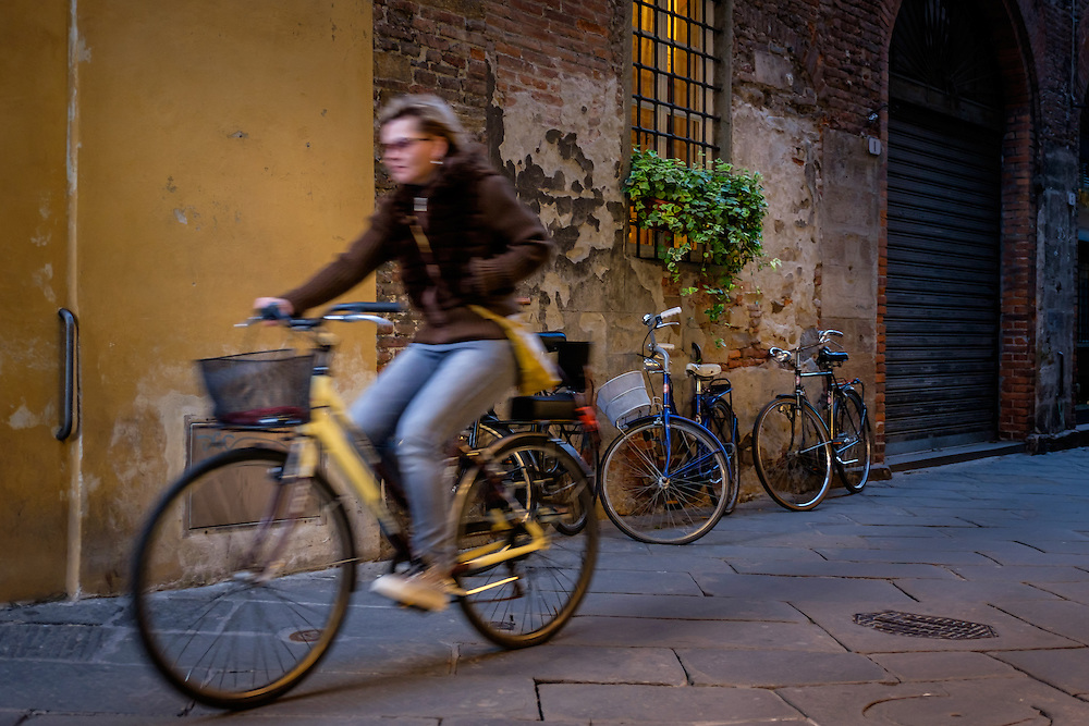 LUCCA ITALY - CIRCA MAY 2015:  Woman riding a bicycle in the streets of Lucca, a famous medieval town in Tuscany.