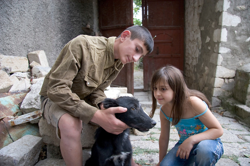 Two of Saro Sarian's children put ointment on a cut on their dog's head, outside the home they claimed in 1998 in Shushi, Nagorno-Karabakh.