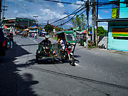 "31 JANUARY 2018 - LEGAZPI, ALBAY, PHILIPPINES: ""Tricycle taxis"" on the streets of Legazpi, Philippines. Tricycle taxis are motorcycles with sidecars, similar to tuk-tuks and trishaws found in other countries in Asia.        PHOTO BY JACK KURTZ"