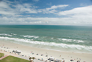 Blue sky with clouds, blue ocean with surf and beach with umbrellas and beachgoers, Daytona Beach, Florida.