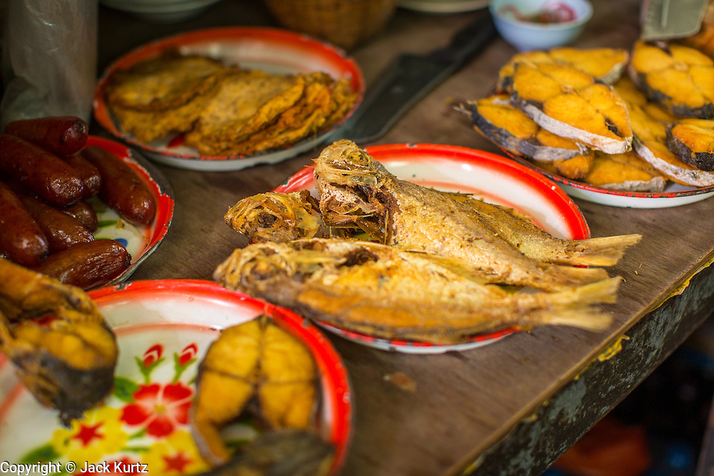 "05 OCTOBER 2012 - BANGKOK, THAILAND: Fried fish for sale on street food vendor's cart. Thailand in general, and Bangkok in particular, has a vibrant tradition of street food and ""eating on the run."" In recent years, Bangkok's street food has become something of an international landmark and is being written about in glossy travel magazines and in the pages of the New York Times.       PHOTO BY JACK KURTZ"
